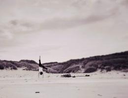woman doing cartwheels at beach