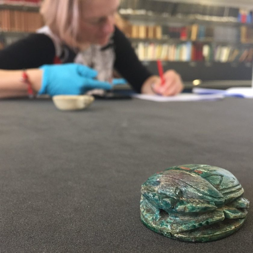 a scarabaei ceramic beetle on a desk in front of image in the background blurred a person writing