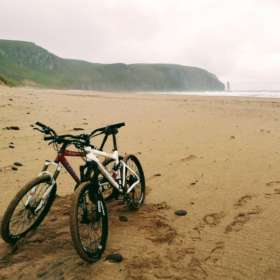 two mountain bikes leaning against each other on the beach