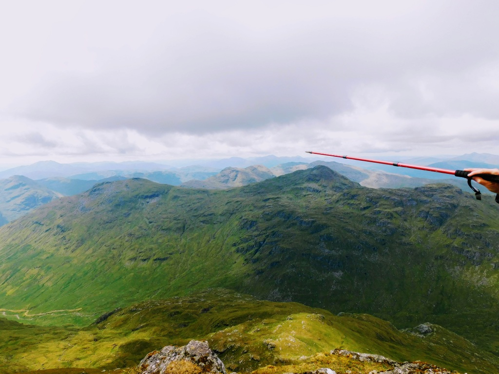 someone using hiking pole pointing across a mountain range