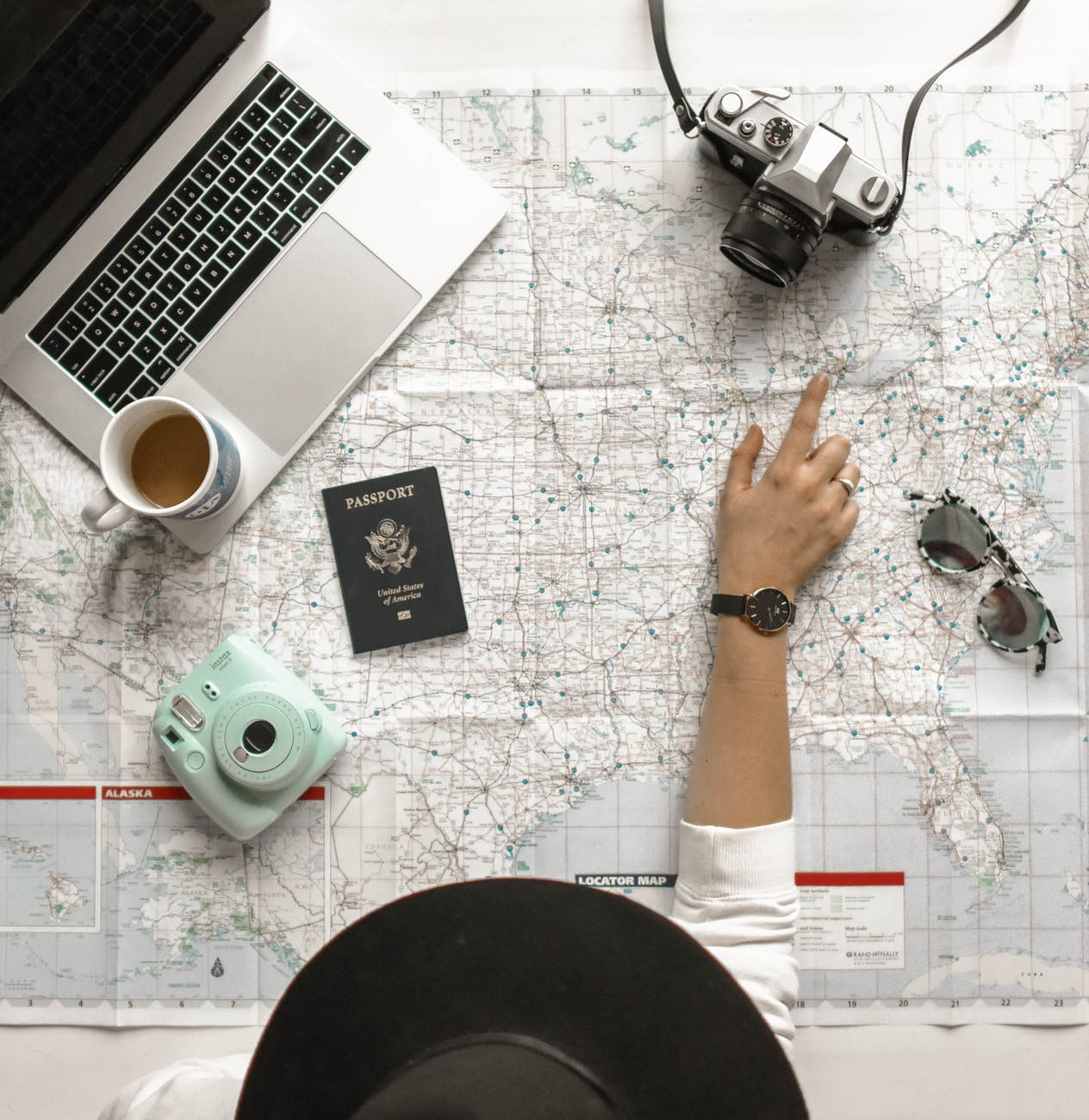 image of person pointing at map a laptop, passport, coffee cup and camera are place on the map. In fact it makes me slightly anxious as the person place the coffee cup on their macbook an accident waiting to happen!
