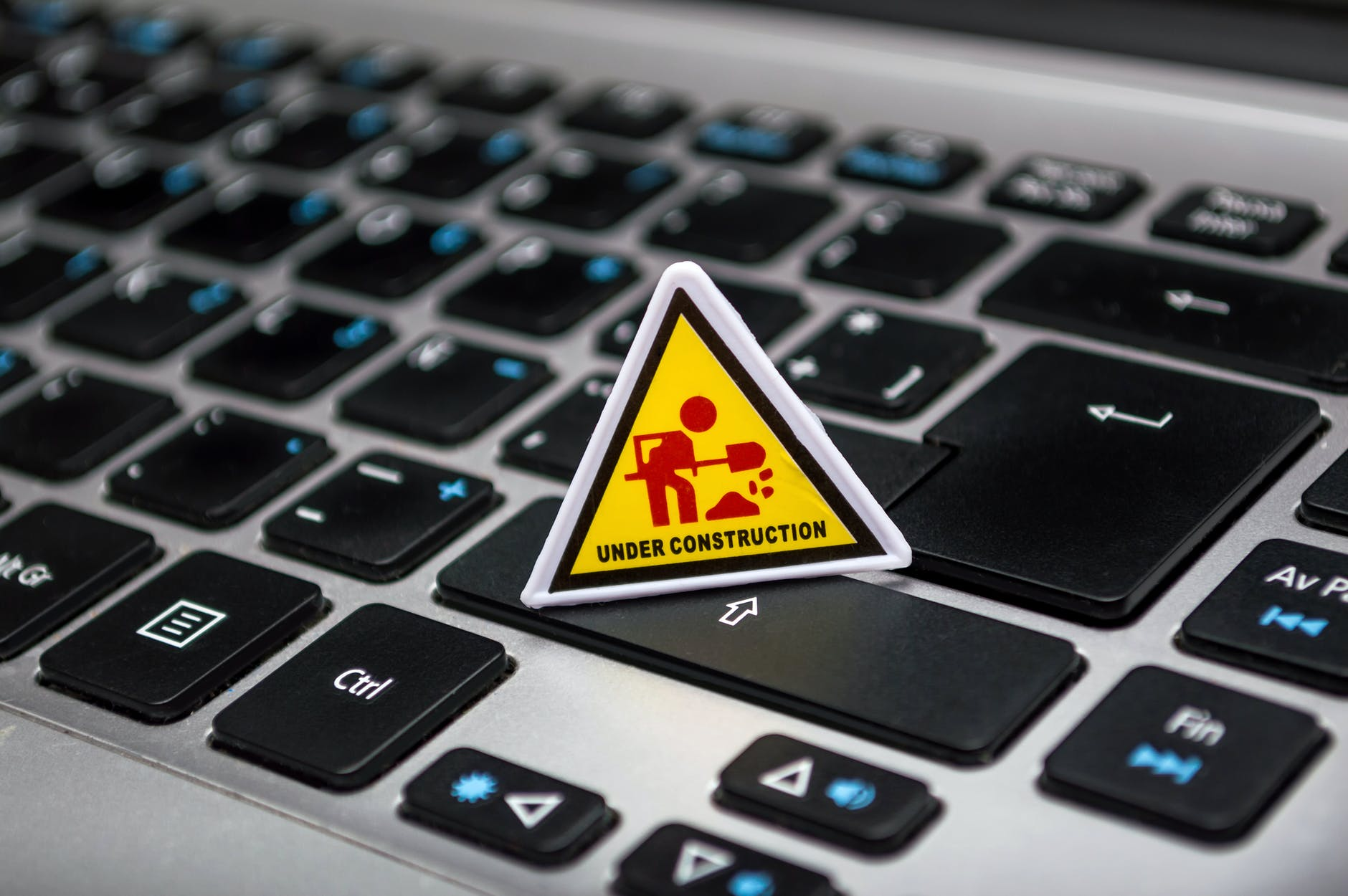an under construction warning triangle placed on a laptop keyboard
