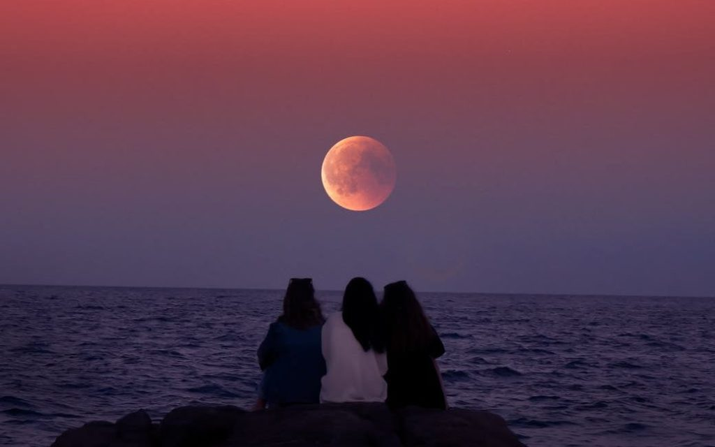 Three women sitting on a rock at the sea shore watching the full moon as it is lid with dramatic sunset colours.