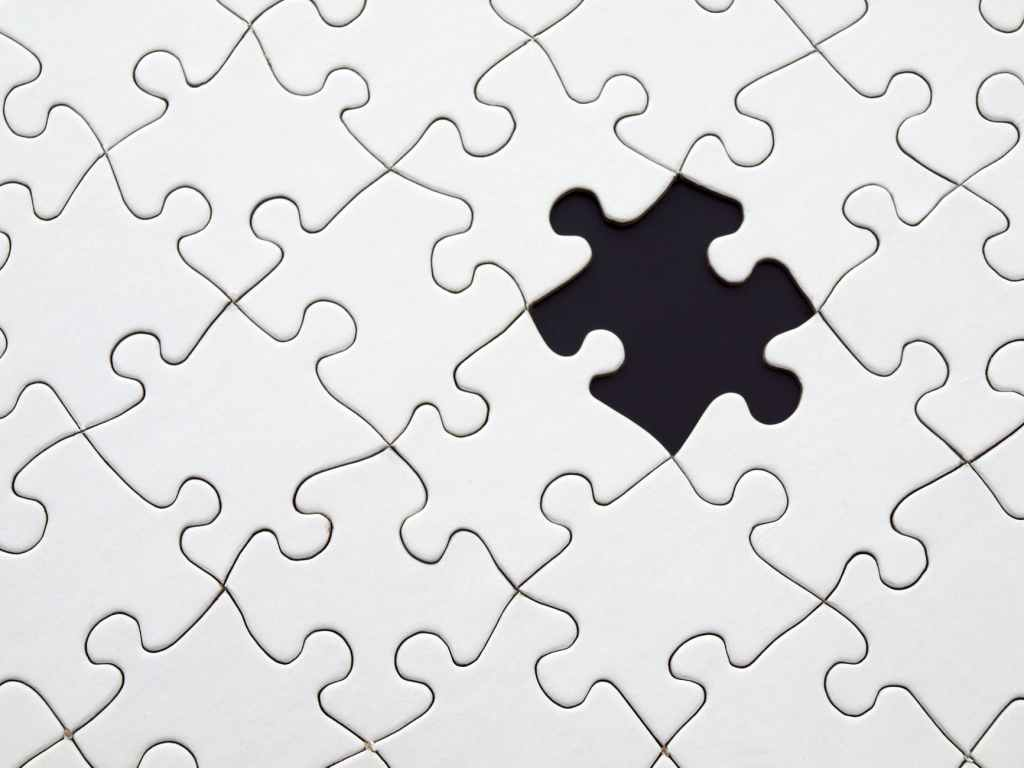 This image shows a jigsaw puzzle without image on it just white one piece is missing which makes it look like there is a black piece in a completely white puzzle