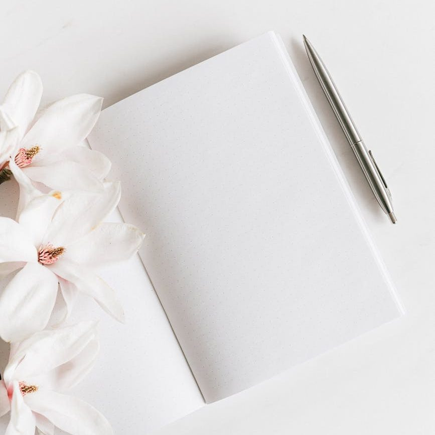 the image shows a white background probaly table top, on which is places an open notebook with pristinely white pages a silver Cross pen is lying to the right of the image the left is page of the notebook is mostly covered by white magnolia blossoms. The arrangement is aligned diagonally to the image frame